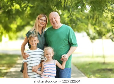 Woman with children and elderly father in park