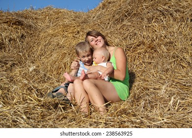 woman with children resting on a haystack