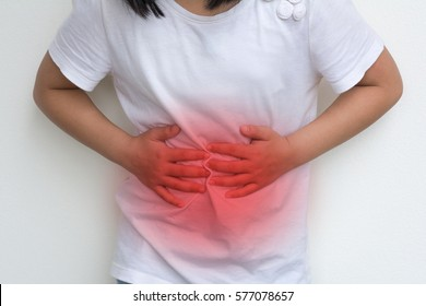 Woman Child's hands on her stomach with red spot as suffering on stomachache. Girl school kid  suffer from Chronic Diarrhea,Digestive Disorders, stomach pain,Crohn's Disease, irritable bowel syndrome