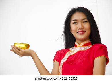 Woman in Chinese traditional dress is holding gold ingot on white background.