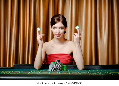 Woman with chips sitting at the roulette table at the casino