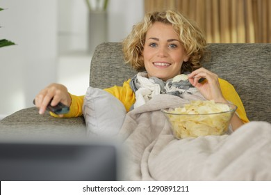 woman with chips watching tv on sofa in living-room