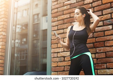Woman choose music to listen in her mobile phone during workout in city, having rest, brick wall background, copy space