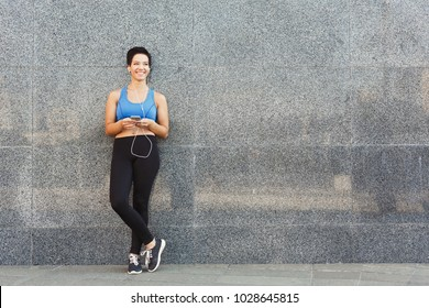 Woman choose music to listen in her mobile phone during workout in city, having rest and leaning at gray wall, copy space