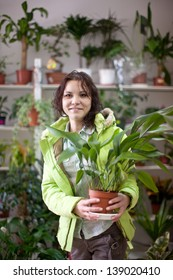 Woman chooses aspidistra flower in a flower shop