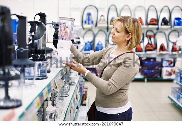 Mujer elige una licuadora en la tienda