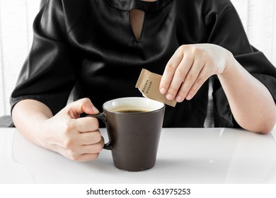 Woman chooses brown sugar puts in the coffee