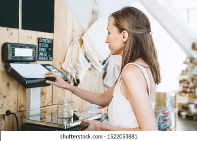 Woman chooses and buys products in zero waste shop. Weighing dry goods in plastic free grocery store. Girl with cotton reusable bag weigh glass jars on scales. Eco shopping at local business
