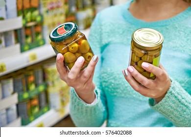 Une femme choisit des olives en conserve à l'épicerie