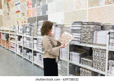 A woman chooses a ceramic tile in a store