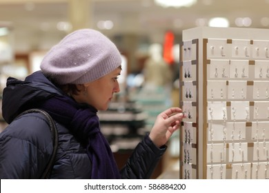 The woman chooses an earrings in the department store