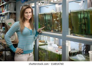 Woman chooses  fish in aquariums at pet-shop