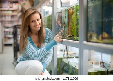 Woman chooses  fish tank in pet-shop