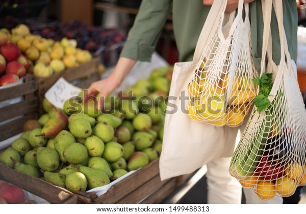 Woman chooses fruits and vegetables at farmers market. Zero waste, plastic free concept. Sustainable lifestyle. Reusable cotton and mesh eco bags for shopping