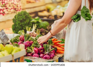 Woman is chooses  fruits and vegetables at food market. Reusable eco bag for shopping. Zero waste concept.