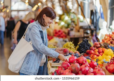 Woman is chooses fruits and vegetables at food market. Reusable eco bag for shopping. Sustainable lifestyle. Eco friendly concept.
