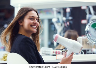 Woman chooses a hairdryer in the store
