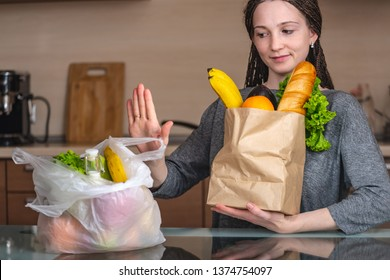 A woman chooses a paper bag with food and refuses to use plastic on the background of the kitchen. Concept of environmental protection and the abandonment of plastic