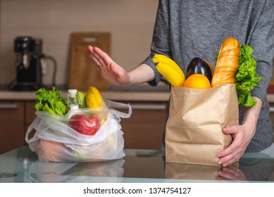 A woman chooses a paper bag with food and refuses to use plastic on the background of the kitchen. The concept of environmental protection and the abandonment of plastic