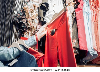 woman chooses red pants in the store. girl buys clothes in boutique