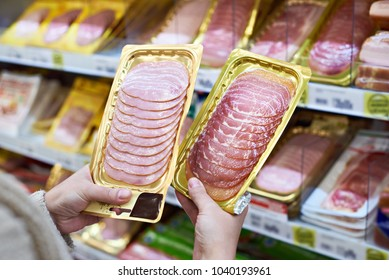 Woman chooses a slice of ham and meat  in vacuum package at the grocery store