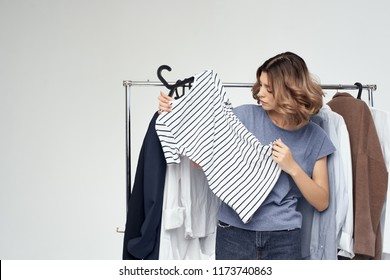 woman chooses things on her shoulders in the dressing room