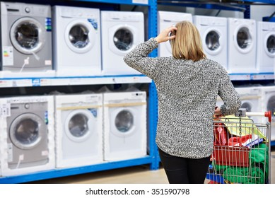 Woman chooses washing machine in the shop of home appliances