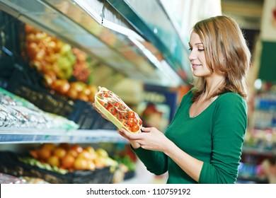 woman choosing apple during shopping at fruit vegetable supermarket