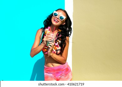 Woman choosing the bag from many colorful bags.Isolated on light blue background.Shopping addiction.Beautiful girl with long wavy hair.Brunette with curly hairstyle,laughing and smiling,crazy emotions