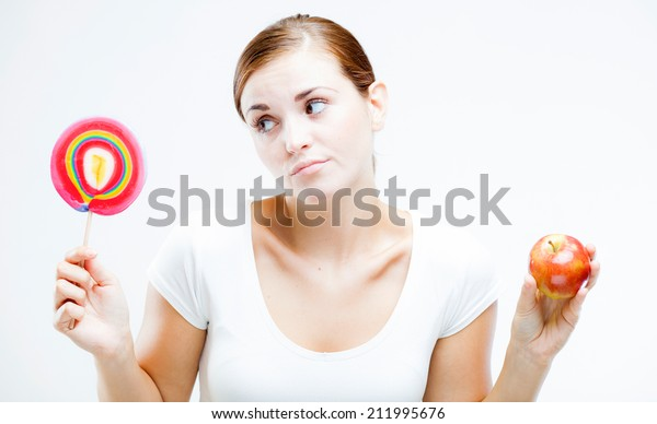 Woman choosing between sweets and fruits, healthy or unhealthy food concept