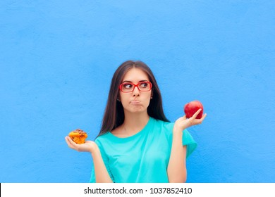 Woman Choosing Between Unhealthy Muffin and Healthy Apple. Girl comparing dessert options having a hard time choosing