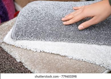 Woman choosing carpet, closeup