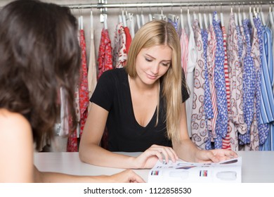 Woman choosing clothes from a catalogue in a shop