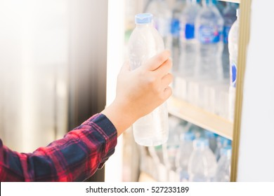 woman choosing cold  bottle of water or beverage on shelves in supermarket store.
