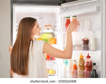 Woman choosing food in refrigerator at home