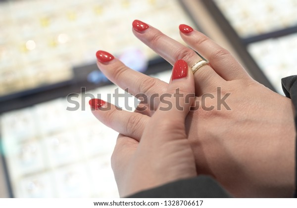 A woman is choosing a gold wedding ring in a jewelry store.