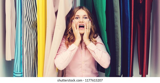 Woman choosing her fashion outfit. Sale, gifts, holidays and people concept. Girl thinking what to wear in front of many choices of clothes in organized wardrobe. Home closet or store clothing rack