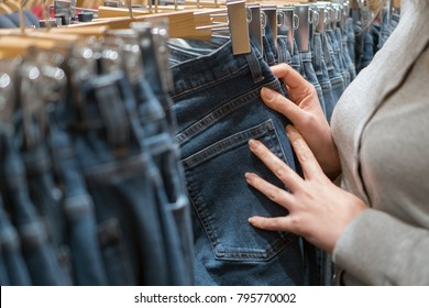 Woman choosing jeans in clothing store.