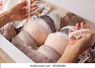 Woman choosing lingerie. Drawers filled with sexy lace lingerie. Textile, Underwear.