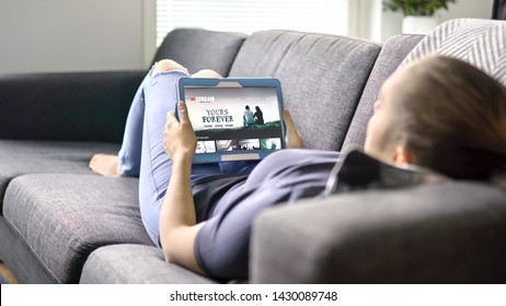Woman choosing movie from online stream service with tablet. Watching series with on demand video (VOD) website concept. Streaming digital film from site by tv network. Mockup on smart device screen.