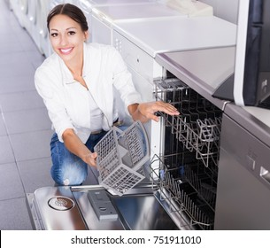 Woman choosing new dish washing machine in supermarket