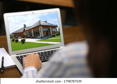 Woman choosing new house online using laptop or real estate agent working at table, closeup