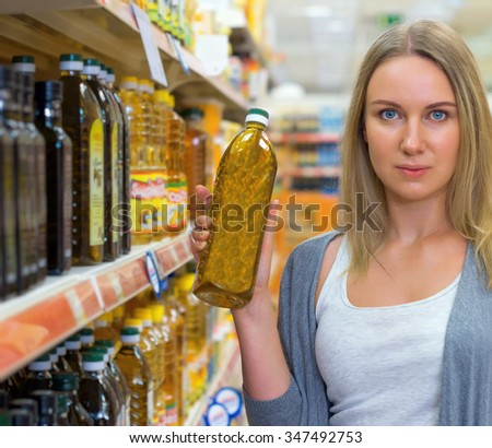 Woman choosing olive oil in grocery store.