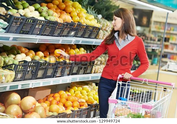 woman choosing orange or mandarin during shopping at fruit vegetable supermarket