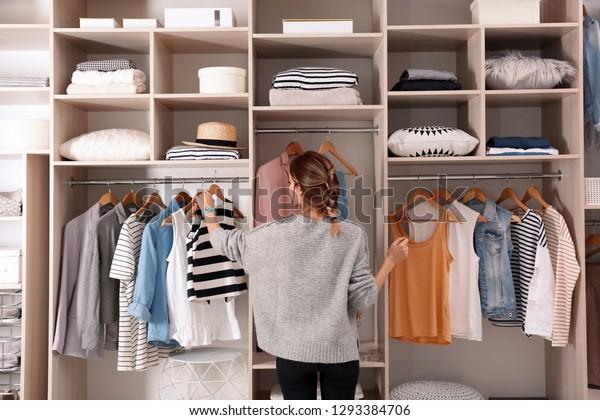 Mulher escolhendo roupa de armário grande com roupas elegantes e coisas caseiras