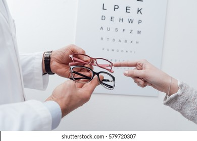 Woman choosing a pair of glasses after the eye exam, the optician is giving her an advice