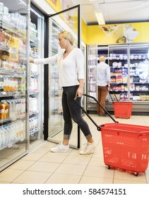 Woman Choosing Product From Refrigerator In Supermarket