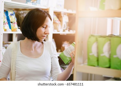 Woman choosing products in ecological shop with healthy food and reading product information on label