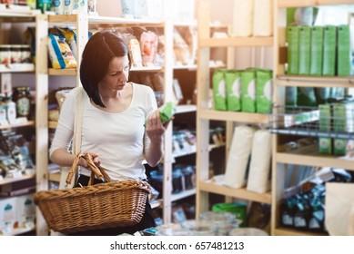 Mulher escolhendo produtos em loja ecológica com alimentos saudáveis e lendo informações sobre o produto no rótulo
