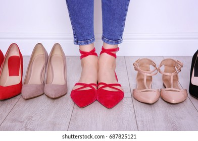 Woman choosing shoes on light background